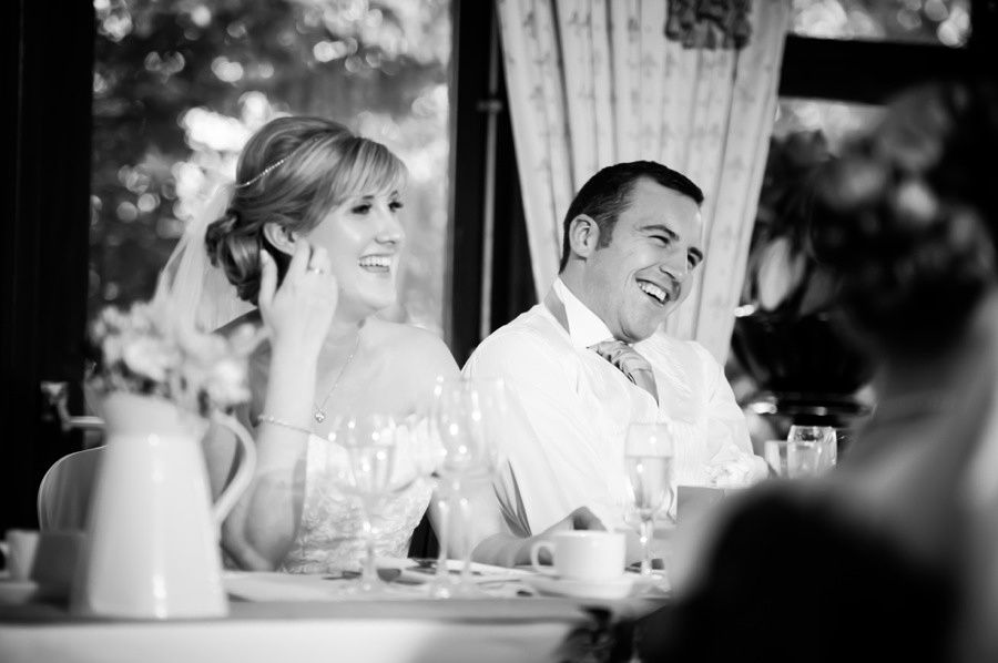 Bride and Groom laughing at Wedding Reception by North Wales Wedding Photographer Celynnen Photography