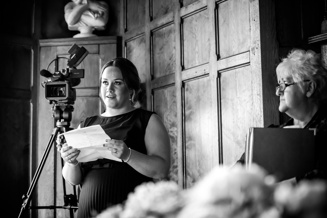 Black and white image of someone giving a speech during a wedding ceremony at Chateau Rhianfa.