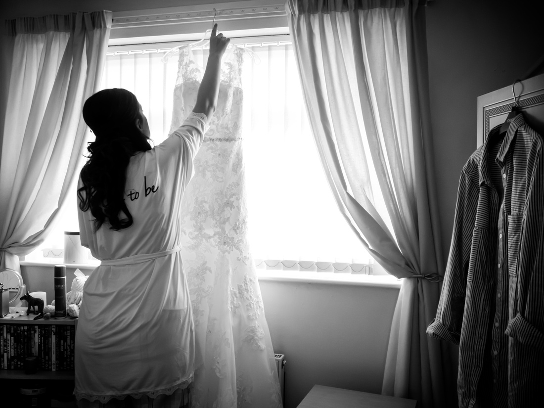 Black and white image of bride hanging up her wedding dress before heading to the wedding venue, Chateau Rhianfa.