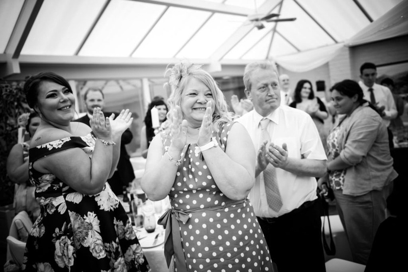 Black and white image of the guests applauding the bride and groom's entrance to the wedding reception at The Lion Quays.