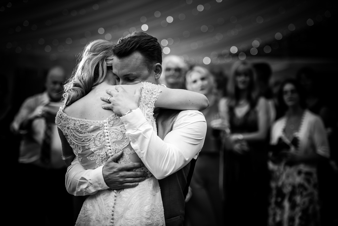 Bride and groom hugging during their first dance on their wedding day at Bodrhyddan Hall by wedding photographer Celynnen Photography