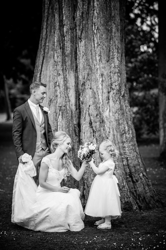 Image of the bride and groom interacting with the flower girl at Bodrhyddan Hall.