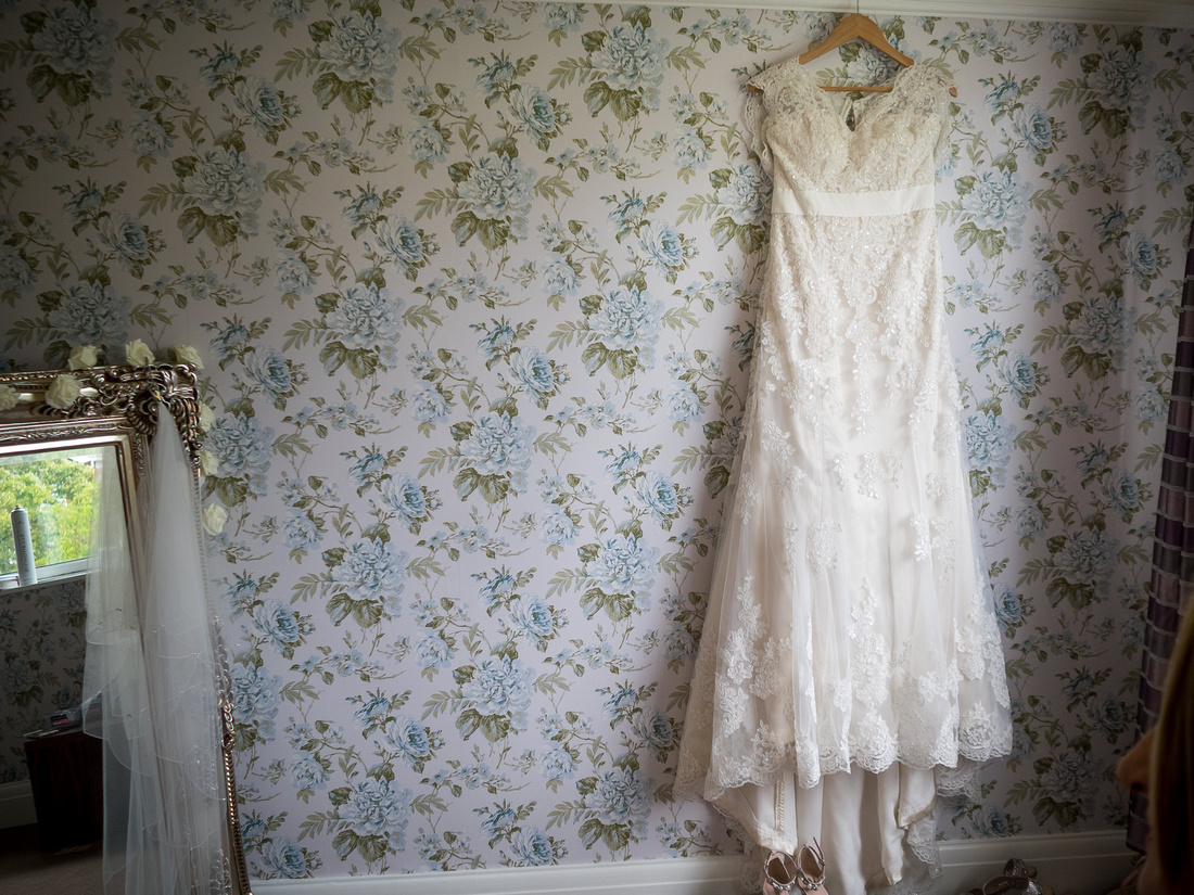 Photograph of the bride's dress hanging up before heading to The Kinmel for their wedding day.