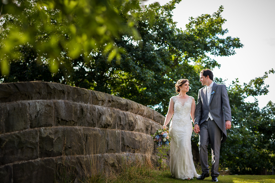 Image of a newly married couple taking a stroll on their wedding day around the grounds of Tower Hill Barns.