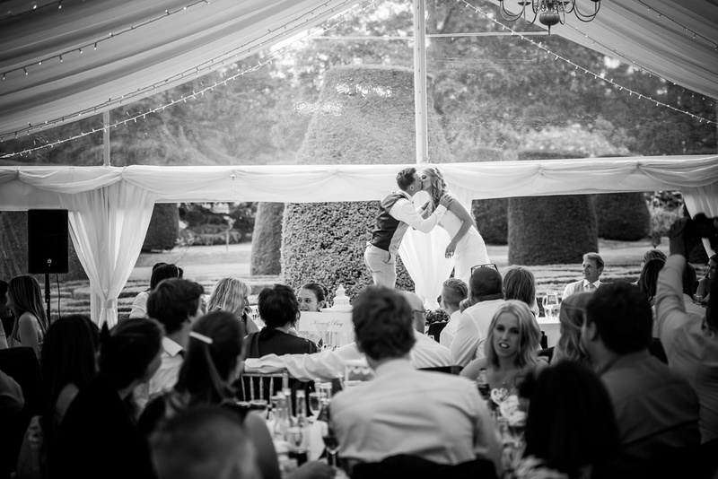Black and white image of the bride and groom kissing in front of all their family and friends at Bodrhyddan Hall.