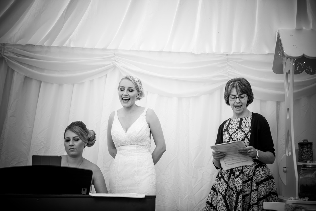 Black and white image of the bride singing on her wedding day during her reception at Pentre Mawr.