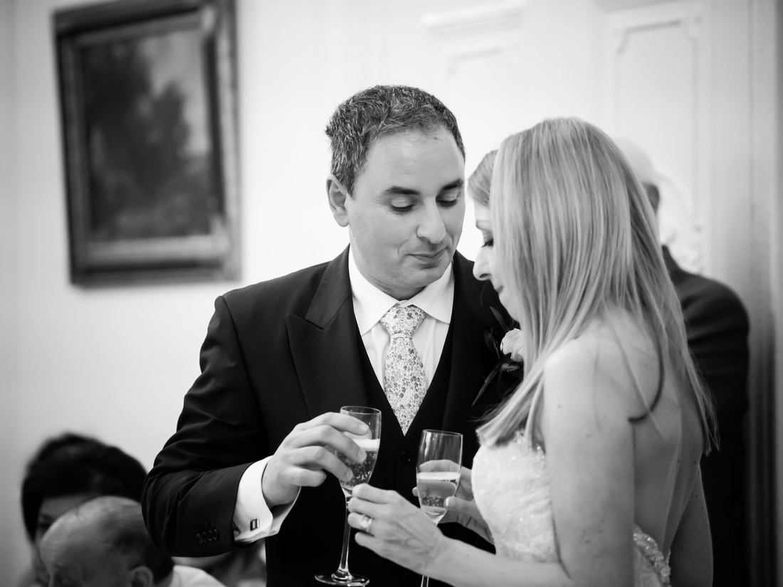 Black and white image of the bride and groom during the speeches at a wedding at Taplow House, Buckinghamshire.