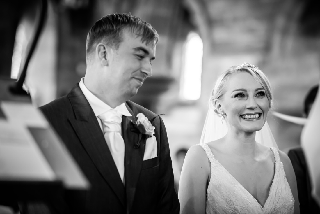 Black and white image of the bride and groom enjoying their wedding ceremony in a church in Halkyn.