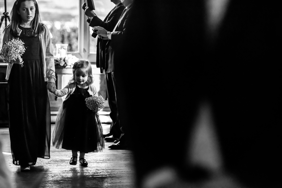 Black and white image of some bridesmaids walking down the aisle at a wedding at Chateau Rhianfa.