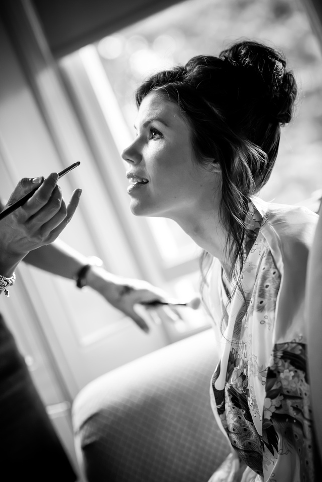 Black and white image of the bride getting her make up done in her preparations for her special day at Ruthin Castle.