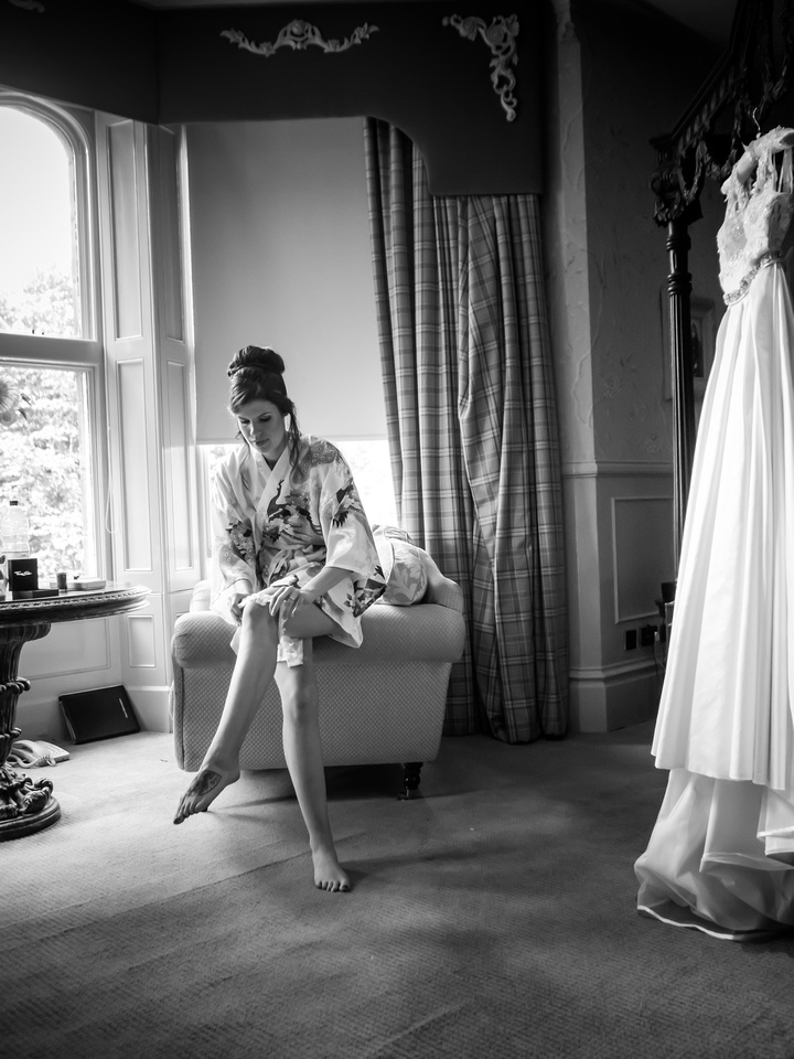 Black and white image of the bride putting on her wedding garter before getting dressed into her wedding dress, at Ruthin Castle.