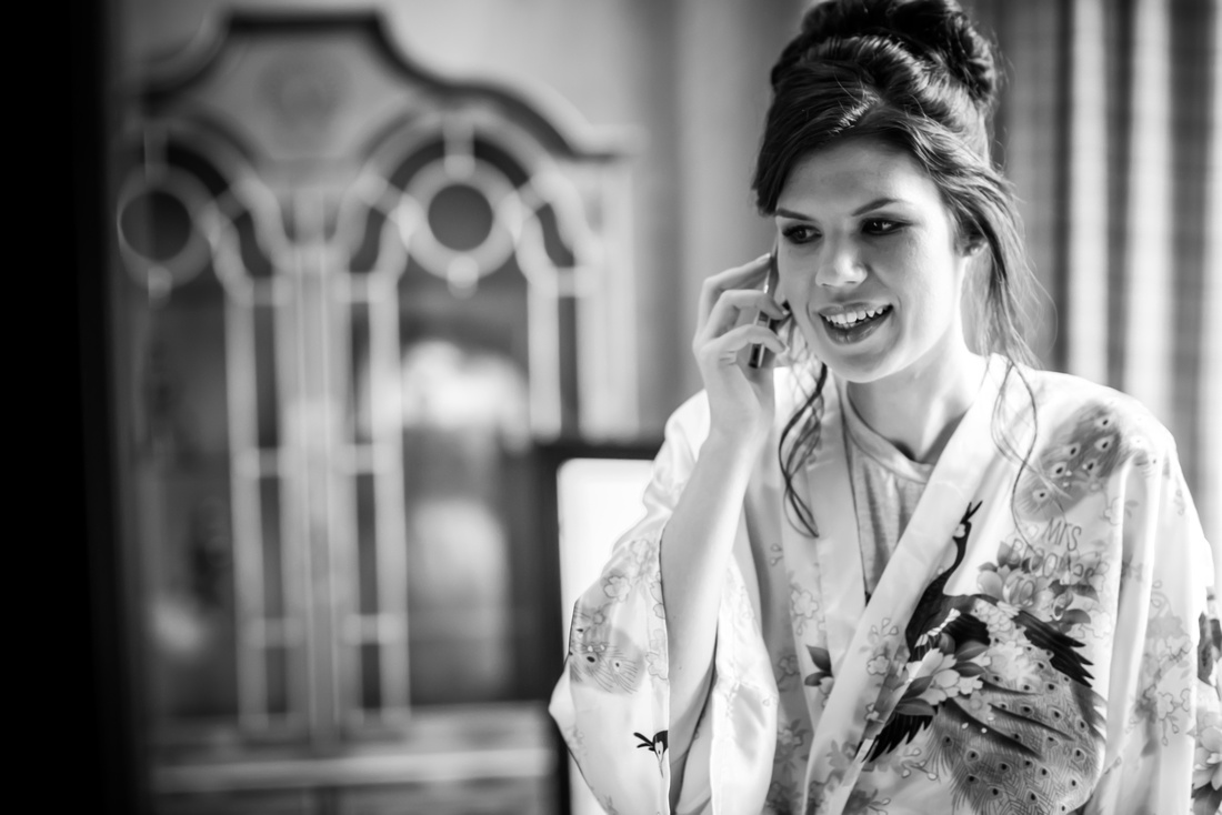 Black and white image of the bride talking on the phone during her bridal preparations at Ruthin Castle.
