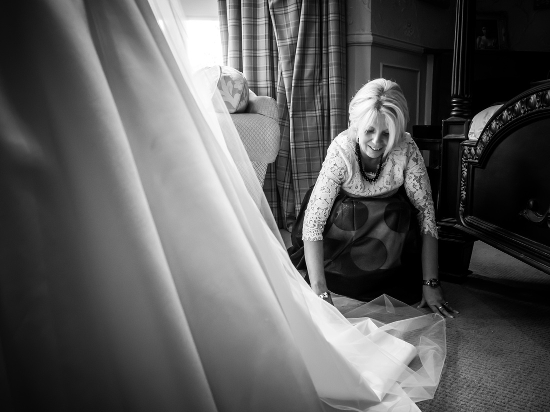 Black and white image of the mother of the bride helping her daughter get ready for her wedding day at Ruthin Castle.