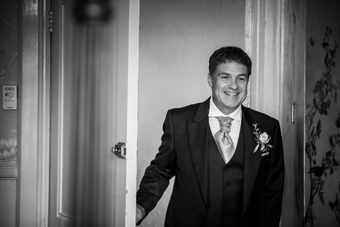 Black and white image of the father of the bride seeing his daughter for the first time as a bride. Wedding at Ruthin Castle.