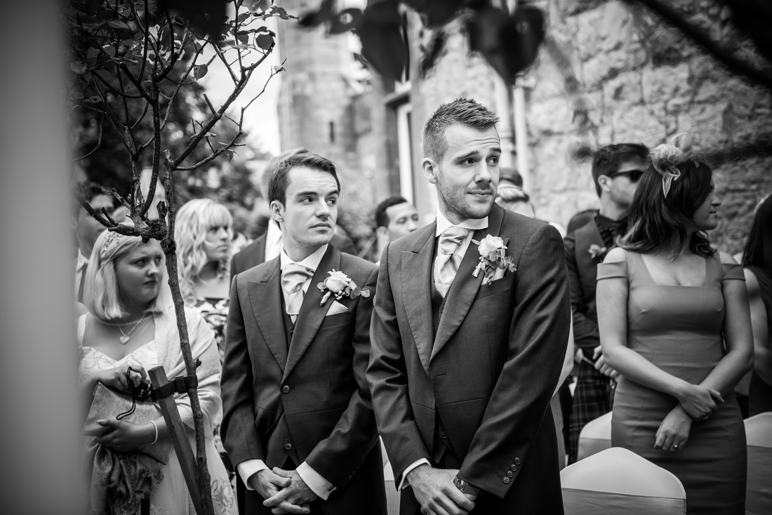Black and white image of two of the ushers waiting for the bride to come down the aisle. Wedding at Ruthin Castle.
