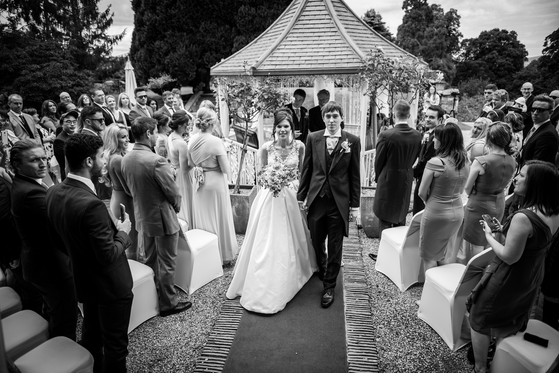 Black and white image of the bride and groom leaving their wedding ceremony as a married couple. Wedding at Ruthin Castle.