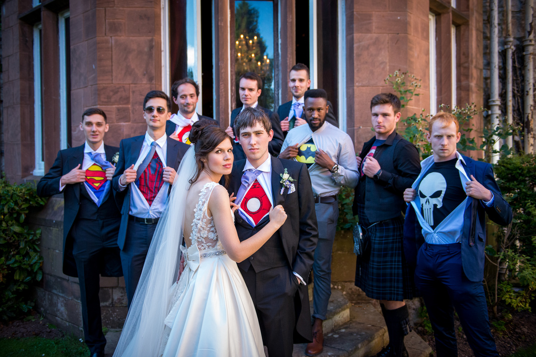 Image of the groom and ushers showing off their marvel superheroes shirts under their wedding outfits at a wedding at Ruthin Castle.