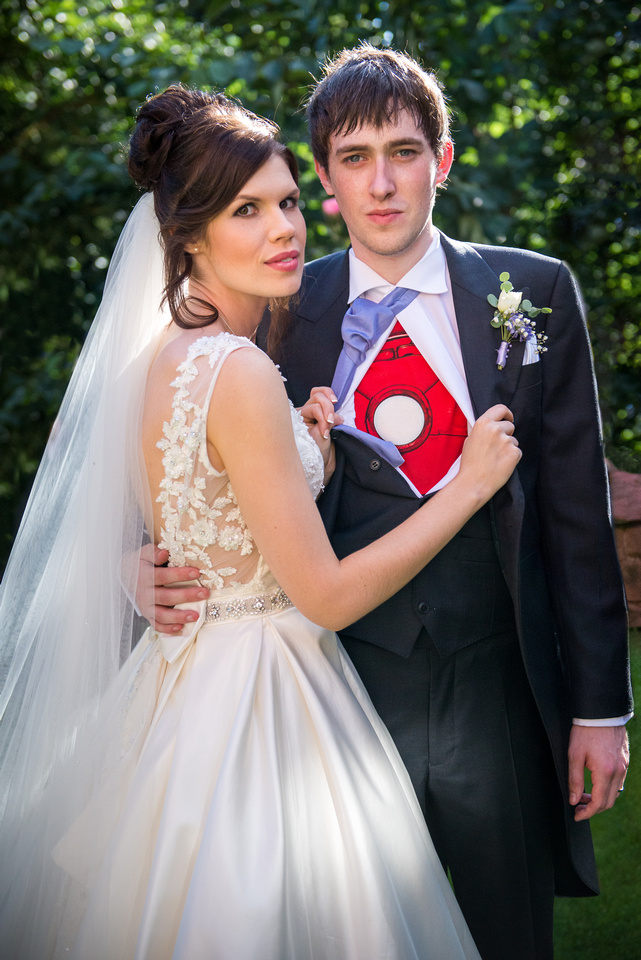 Portrait of the bride with her groom, who is showing off his marvel superhero shirt under his wedding suit at a wedding at Ruthin Castle.