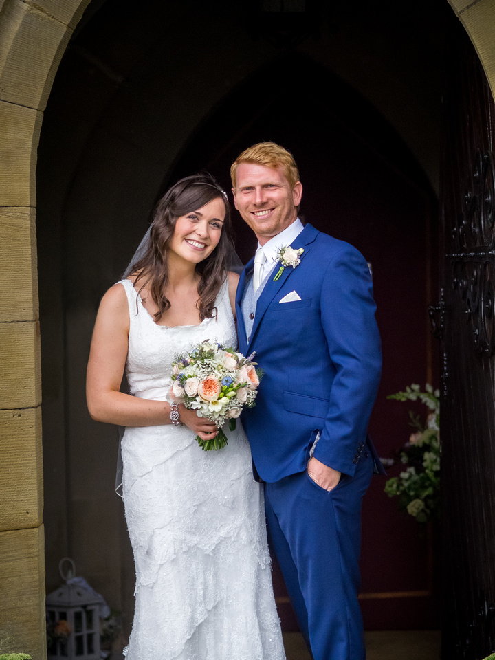 Portrait of the bride and groom after their wedding ceremony at a church in Llandegla.