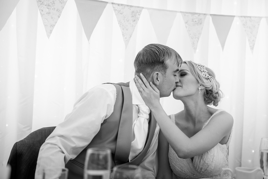 Black and white image of the bride and groom sharing a kiss after the groom's speech on their wedding day at Pentre Mawr.