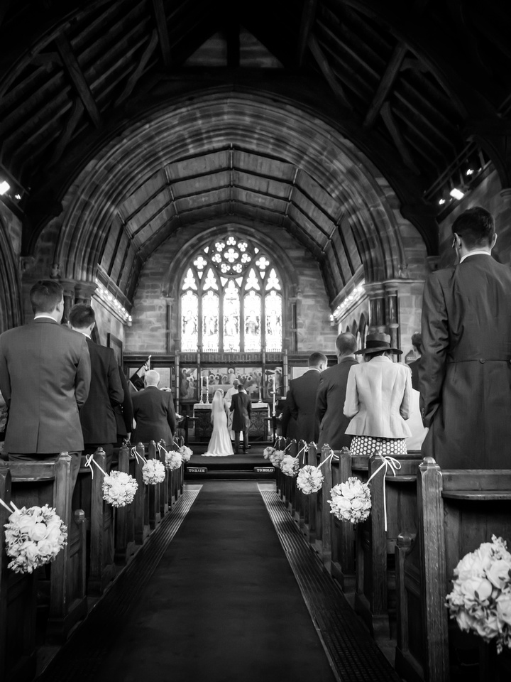 Black and white image from the back of the church during the wedding ceremony. Location is Halkyn.