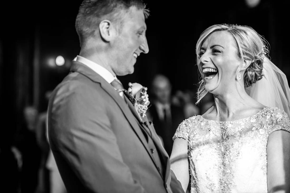Black and white image of the bride and groom laughing during their wedding ceremony in Portmeirion.