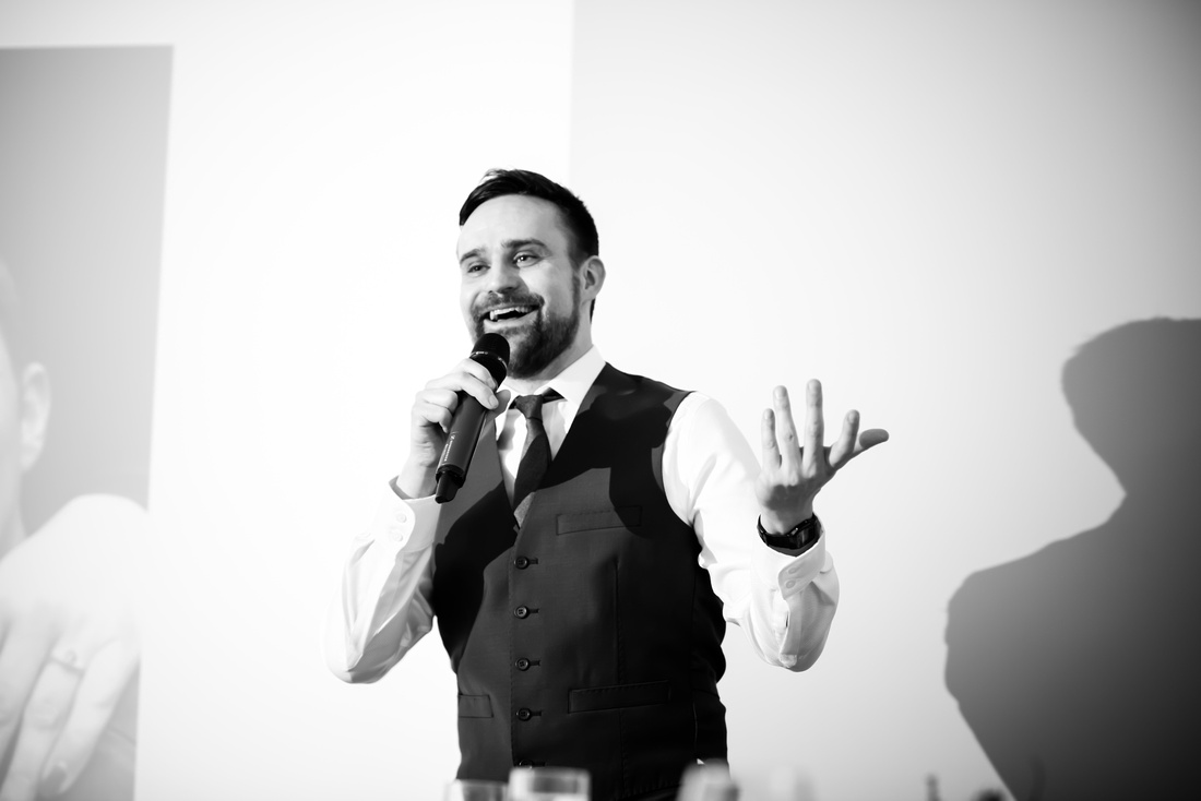 Black and white image of the best man giving his speech at a wedding at Beeston Manor.
