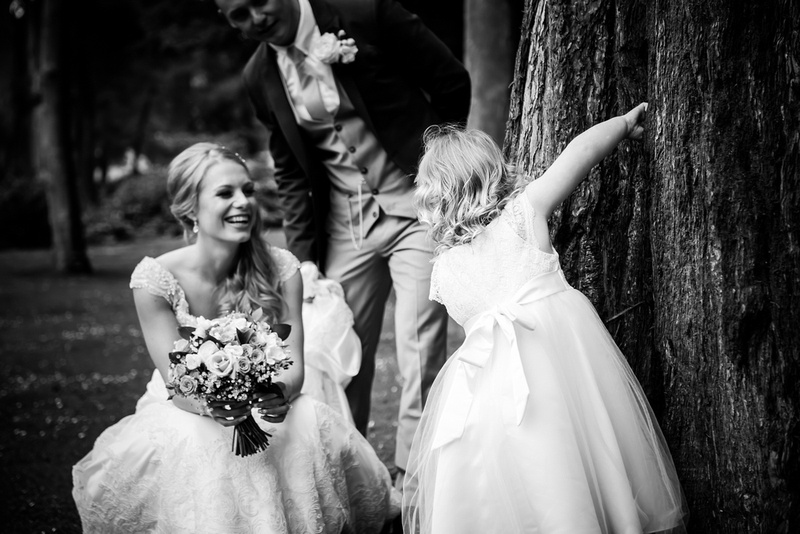 Black and white image of the bride and groom interacting with the flower girl at Bodrhyddan Hall.