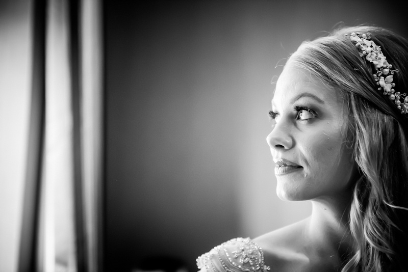 Black and white image of the bride gazing out of the window on her wedding day.
