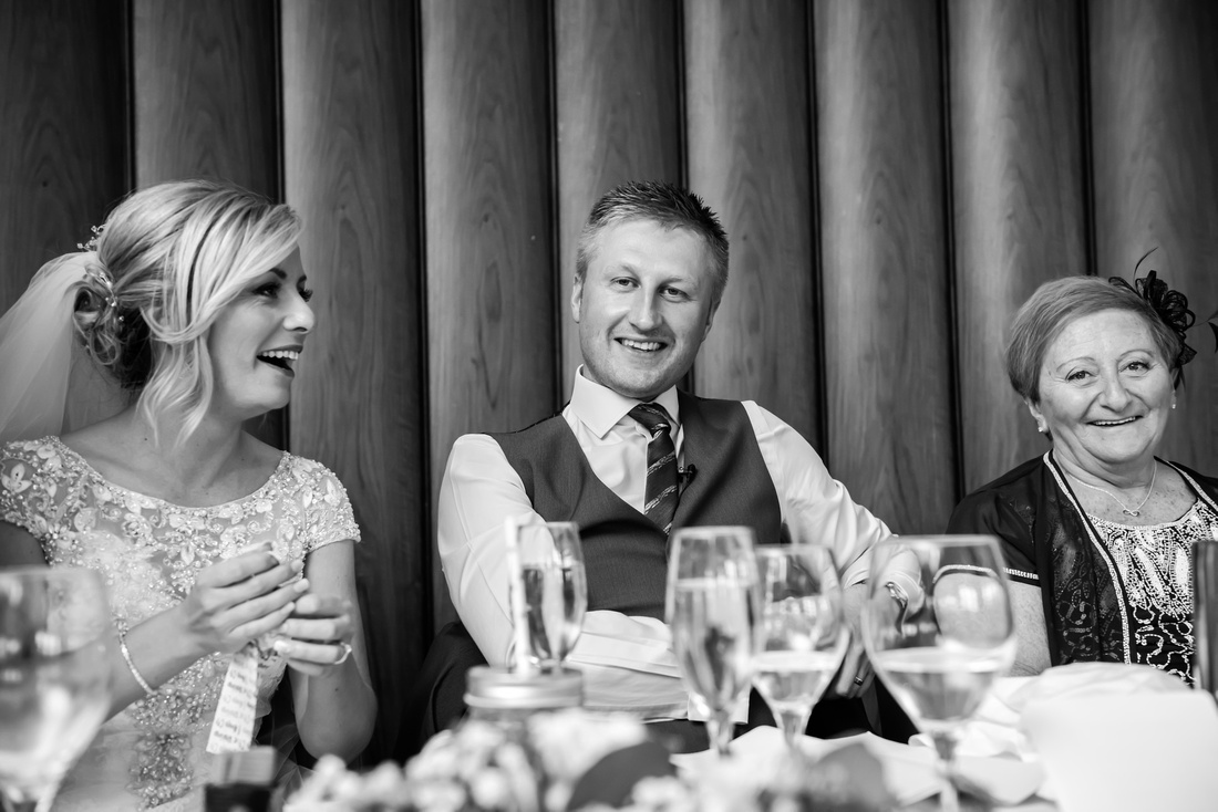 Black and white image of the groom enjoying the speeches at his wedding at Portmeirion.