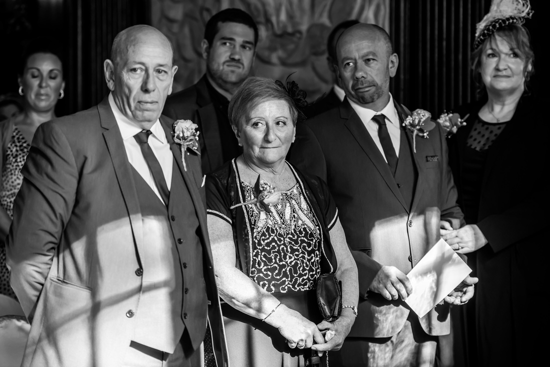 Black and white image of some of the guests during a wedding ceremony in Portmeirion.