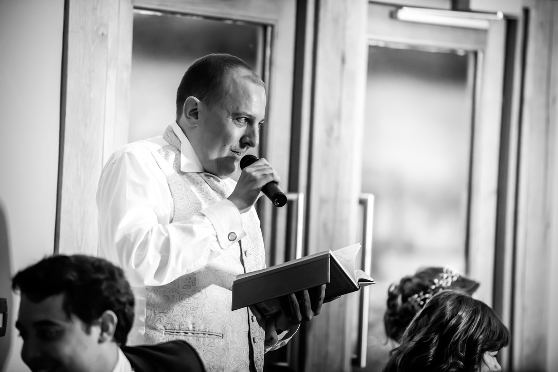 Black and white image of the best man giving his speech during the wedding reception at Tower Hill Barns.