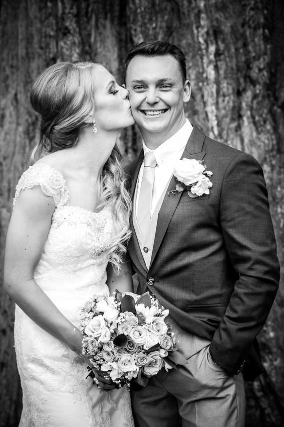 Black and white image of the bride kissing the groom's cheek at Bodrhyddan Hall.