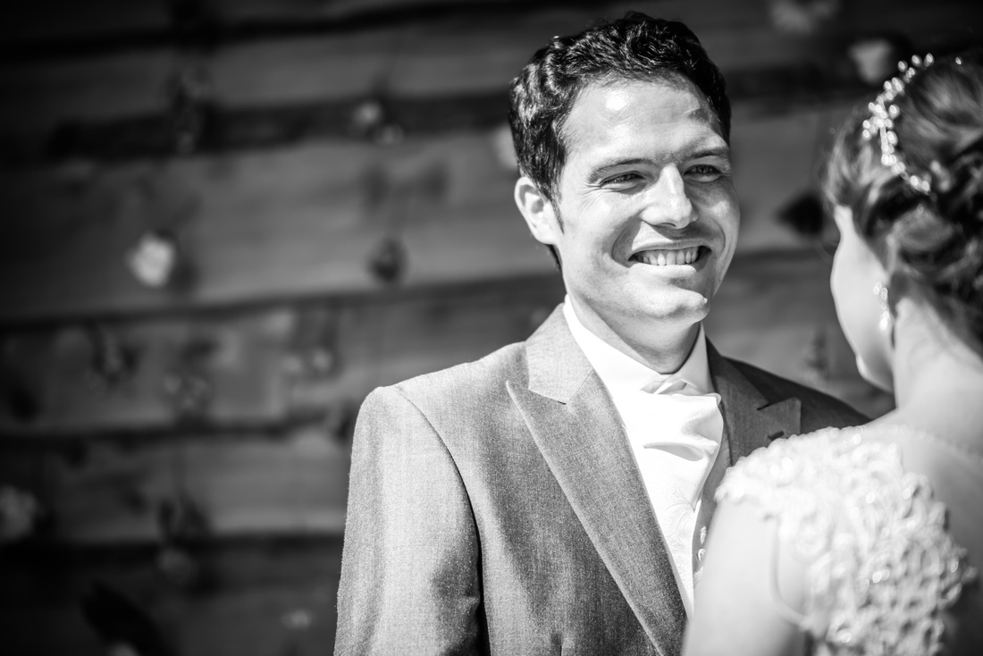 Black and white image of a groom gazing at his bride during a wedding ceremony at Tower Hill Barns.