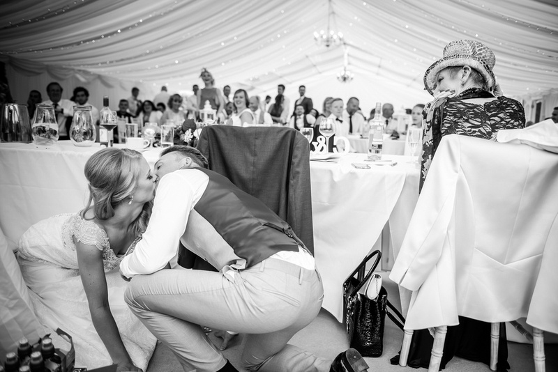 Black and white image of the married couple sharing a kiss behind the table at their wedding reception at Bodrhyddan Hall.
