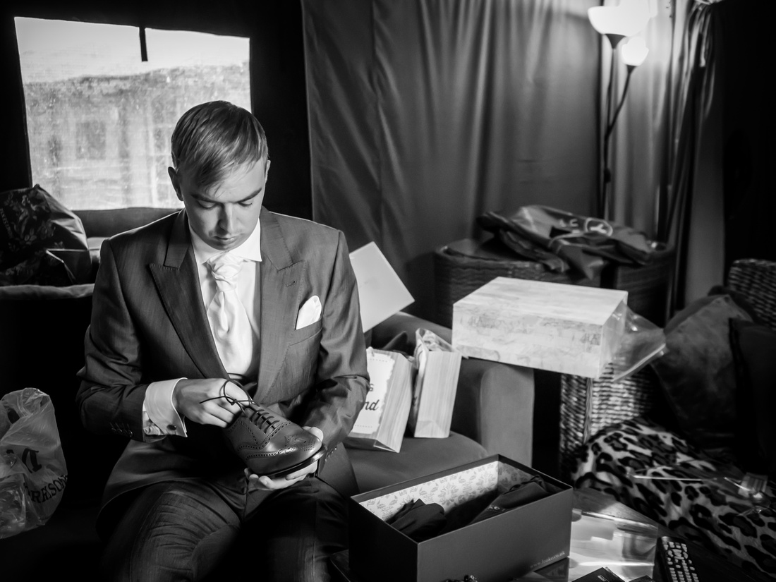 Black and white image of the groom getting ready and preparing to put on his shoes. Wedding at Pentre Mawr.