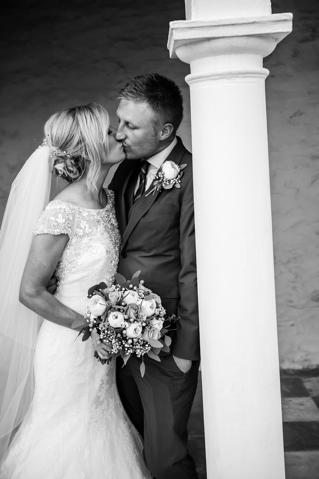 Black and white sharing a kiss during their wedding day in Portmeirion.