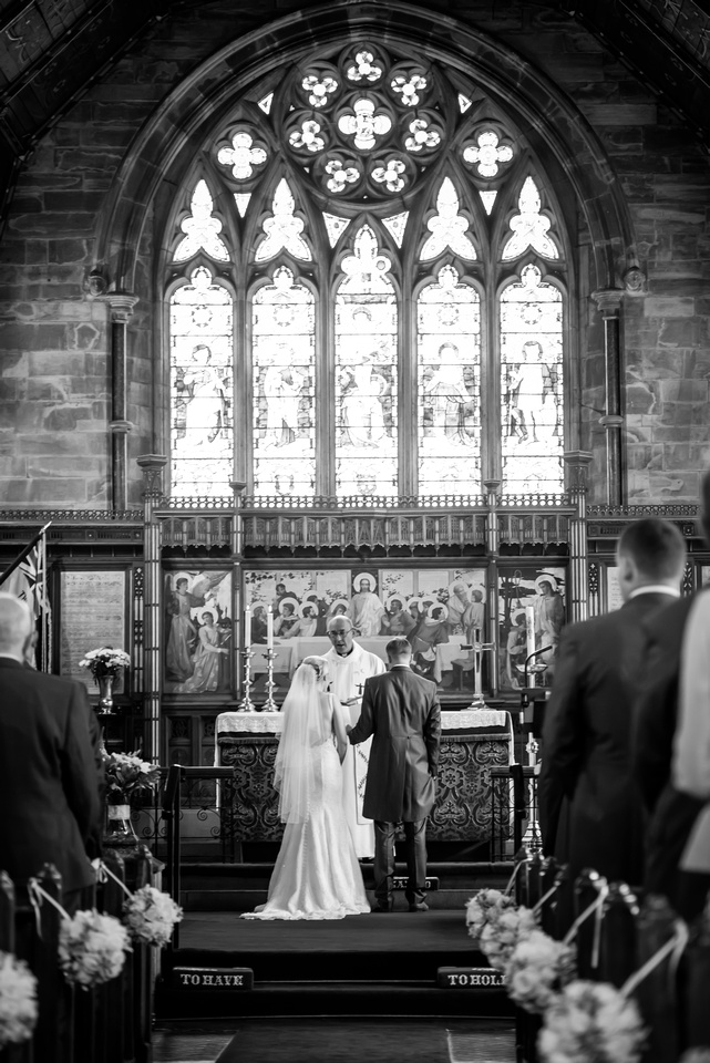 Black and white image of bride and groom standing in front of the stain glass window of a church during a wedding ceremony in Halkyn.