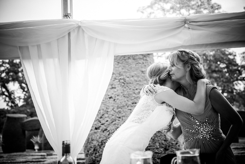 Black and white image of the bride hugging her mother after her parent's speech at Bodrhyddan Hall.