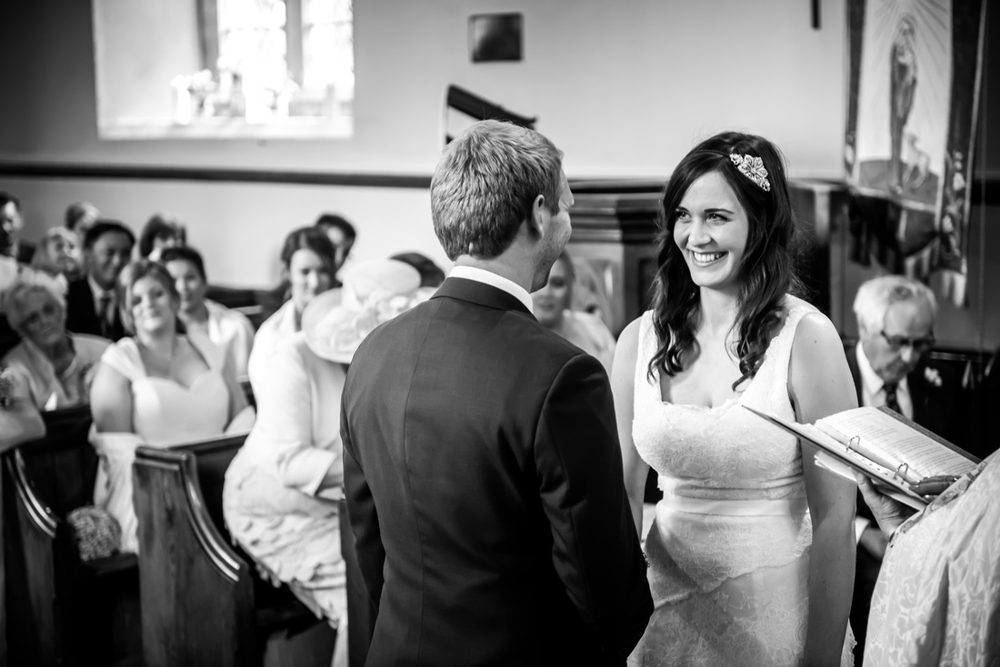 Image of the bride and groom gazing at each other during their wedding ceremony at a church in Llandegla.