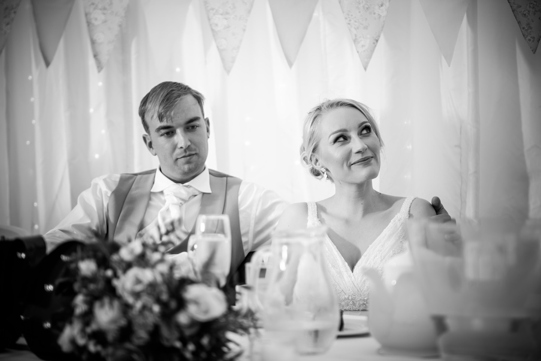 Black and white image of the bride and groom during the speeches on their wedding day at Pentre Mawr.