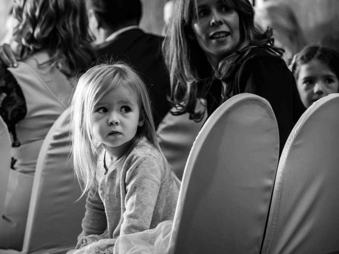 Black and white image of a little girl waiting patiently for the bride to walk down the aisle at a wedding in Portmeirion.