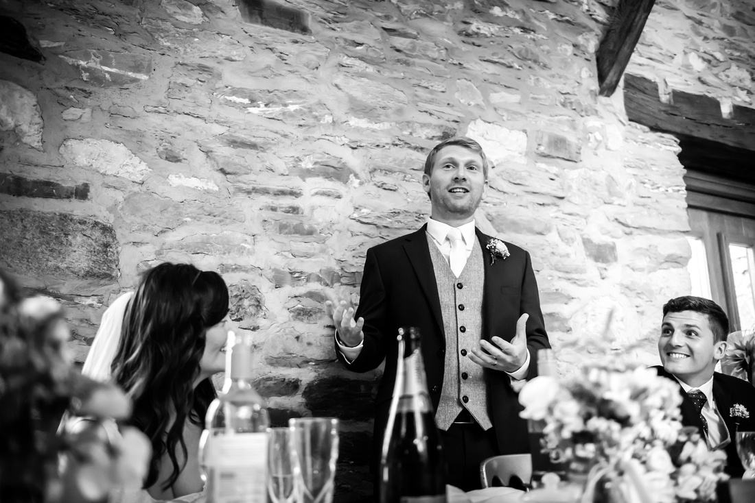Black and white image of the groom during his speech at a wedding at Plas Isaf.