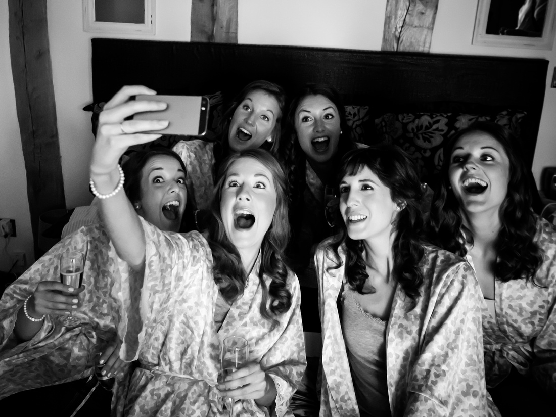 Black and white image of bridesmaids taking a selfie during bridal preparations for a wedding at Tower Hill Barns.