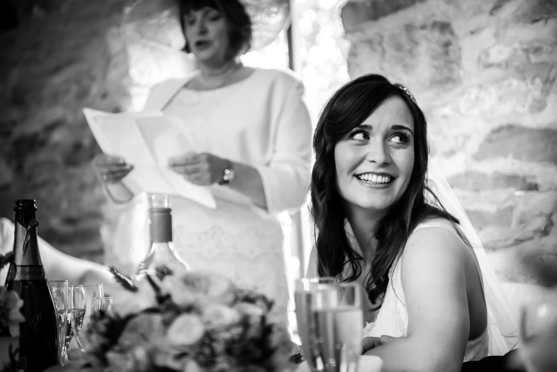 Black and white image of the bride during her mother's speech at a wedding in Plas Isaf.