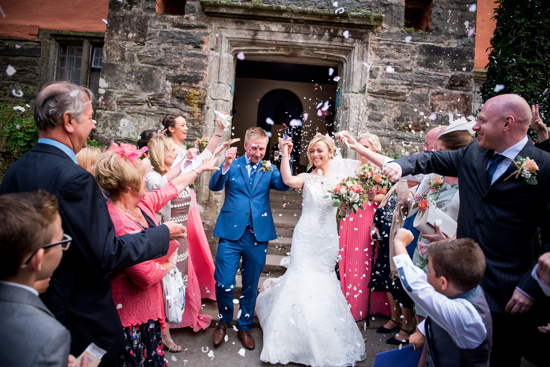 Image of the bride and groom getting showered with confetti after their wedding ceremony in Portmeirion.