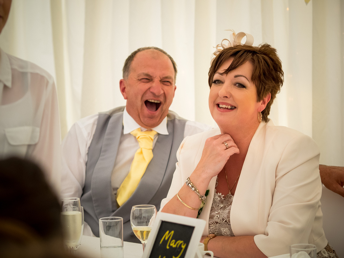 Image of the groom's parents enjoying the speeches at a wedding at Pentre Mawr.