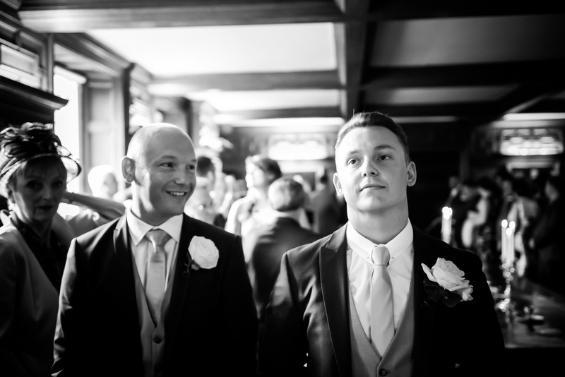 Black and white image of the groom waiting for his bride to walk down the aisle at Bodrhyddan Hall.