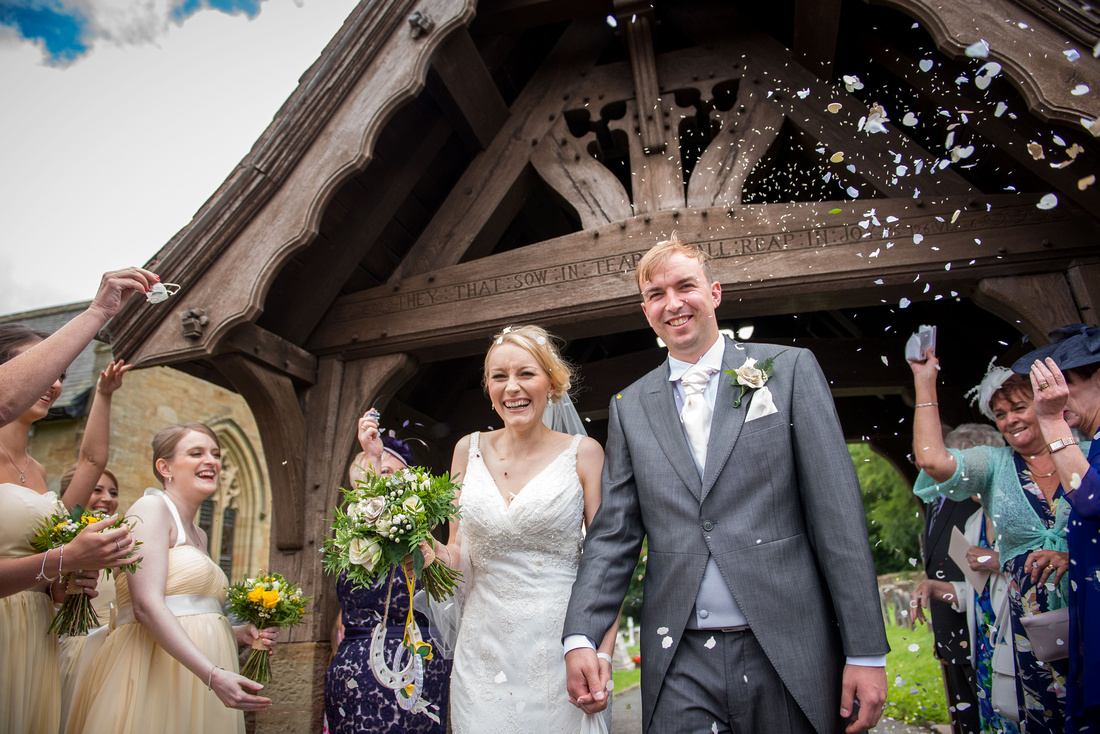 Image of the bride and groom getting showered with confetti outside of the church in Halkyn.