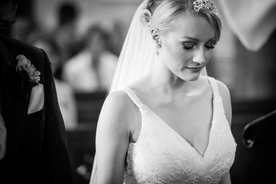 Black and white image of the bride during the wedding ceremony in a church in Halkyn.